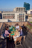 Friends party gathering on rooftop. Group of friends sitting hanging out with drinks on rooftop in urban city Stock Photos