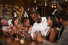 Friends in party hats celebrating New Year at party in a bar Royalty Free Stock Image