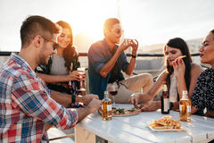 Friends partying and eating pizza. Group of young people sitting around and eating pizza. Friends partying and eating pizza Royalty Free Stock Photography