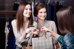Friends pay with credit card. Pretty girlfriends pay with credit card Stock Photo