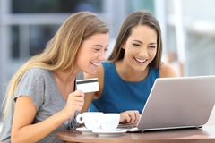 Friends paying on line with credit card in a bar. Two happy friends paying on line with a credit card and a laptop sitting in a bar terrace royalty free stock photos