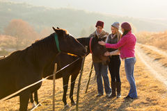 Friends petting horses. Group of friends petting horses in countryside Stock Photo