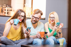Friends with phones at home. Young friends sitting with smart phones on the couch at home Stock Photos