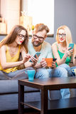 Friends with phones at home. Young friends sitting with smart phones on the couch at home Stock Photography