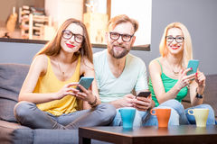 Friends with phones at home. Young friends sitting with smart phones on the couch at home Royalty Free Stock Image