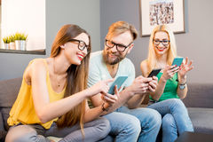 Friends with phones at home Stock Photos