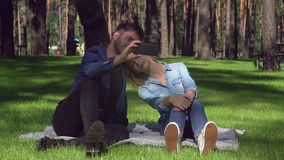 Friends photographed outdoors. Tired woman and smiling man sitting on the grass take selfie photo at the park. Beautiful couple in love have fun on a date stock video