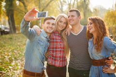 Friends are photographed with a smartphone in the Park. Royalty Free Stock Photography