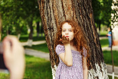 Friends are photographed in the summer park. Curly little girl s Royalty Free Stock Image