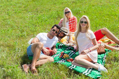 Friends picnic people group sitting blanket outdoor green grass Royalty Free Stock Images