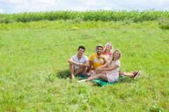 Friends picnic people group sitting blanket outdoor green grass Stock Images