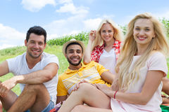 Friends picnic people group sitting blanket outdoor green grass. Two couple summer sunny day blue sky Stock Photos