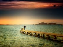Friends on a pier on the beach saying goodbye to summer and vacations stock images