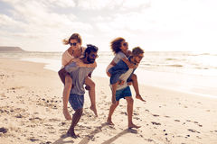 Friends piggyback along the beach stock photography