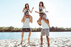 Friends piggybacking and enjoying summertime while spending time on beach. Happy friends piggybacking and enjoying summertime while spending time on beach Stock Image