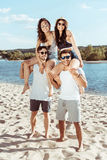 Friends piggybacking and enjoying summertime while spending time on beach. Happy friends piggybacking and enjoying summertime while spending time on beach Royalty Free Stock Photo
