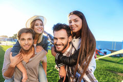 Friends piggybacking in the park stock photography