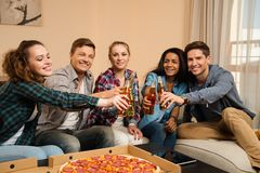Friends with pizza and bottles of drink celebrating Stock Image