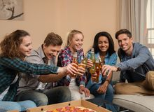 Friends with pizza and bottles of drink celebrating Stock Photos