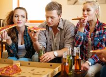 Friends with pizza and bottles of drink Stock Photography