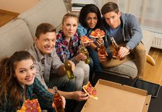 Friends with pizza and bottles of drink having party Royalty Free Stock Image
