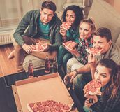 Friends with pizza and bottles of drinks Stock Images