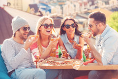 Friends and pizza. Four young cheerful people eating pizza and drinking beer while sitting at the bean bags on the roof of the building royalty free stock photo