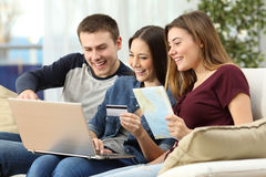 Friends planning and buying a travel on line. Three friends planning and buying a travel on line with a credit card and a laptop sitting on a couch in the living Royalty Free Stock Photography