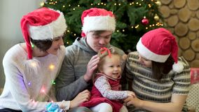 Friends play with little girl, gifts with sparkles and christmas tree background. Christmas holiday. Christmas family stock video