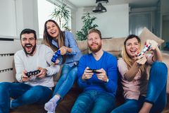 Friends play video games together at home, having fun royalty free stock photography