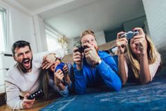 Friends play video games together at home, having fun stock image