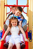 Friends on the playground slide Stock Photos