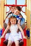 Friends on the playground slide. Three little friends on the playground slide Stock Photos