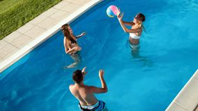 Friends playing ball games in pool. Friends playing ball games in swimming pool royalty free stock photos