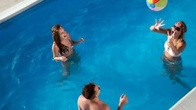 Friends playing ball games in pool. Friends playing ball games in swimming pool royalty free stock photo