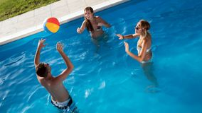Friends playing ball games in pool. Friends playing ball games in swimming pool royalty free stock images