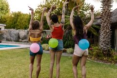 Friends playing balloon bursting game at party Royalty Free Stock Photos