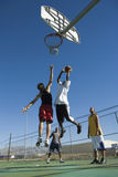 Friends Playing Basketball Against Blue Sky Royalty Free Stock Photos