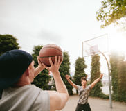 Friends playing basketball against each other. Young men shoots the ball to the basket with friend in background blocking. Friends playing basketball against royalty free stock photo
