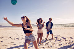 Friends playing beach volleyball. Group of friends playing volleyball on the sandy beach and having fun. Young people on summer holidays playing with ball on the Royalty Free Stock Photography