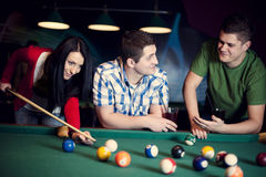 Friends playing billiard Stock Images