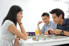Friends playing board game. A group of friend playing a board game at a cafe stock photo