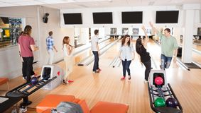Friends Playing in Bowling Alley Stock Image