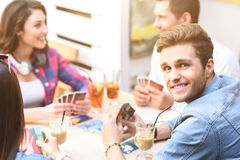 Friends playing card game while sitting at outdoor cafe Stock Images