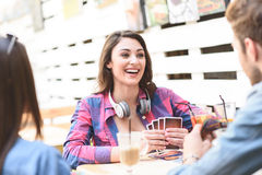 Friends playing card game while sitting at outdoor cafe. Having great day out with my friends. Smiling young girl wearing headphones and sitting at cafe table Stock Image