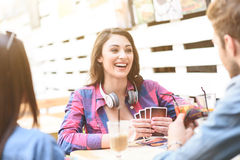 Friends playing card game while sitting at outdoor cafe. Having great day out with my friends. Three friends playing poker at outdoor coffee shop and drinking Royalty Free Stock Image