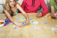 Friends Playing Cards As Woman Grabs Chips Royalty Free Stock Image