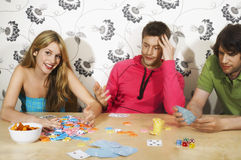 Friends Playing Cards As Woman Wins Stock Photos