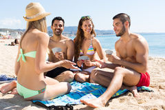 Friends playing cards on the beach. Four smiling persons playing cards sitting on sand summer beach Stock Photos