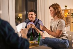 Friends playing cards and drinking beer at home stock photos